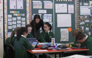 St Francis Xavier Catholic Primary School Ashbury - students working on their laptops with a teacher