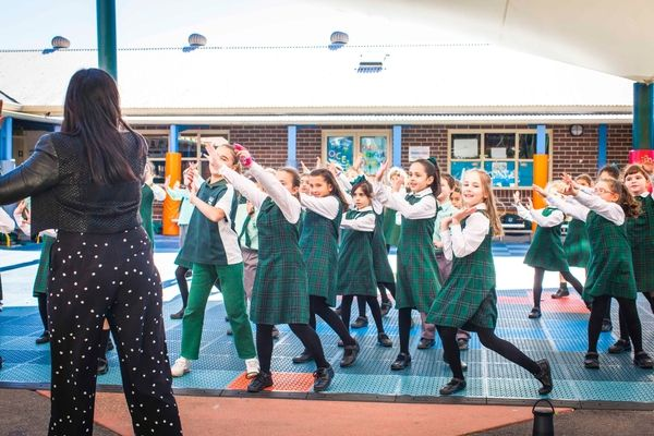 St Francis Xavier Catholic Primary School Ashbury - students dancing in the school courtyard led by teacher