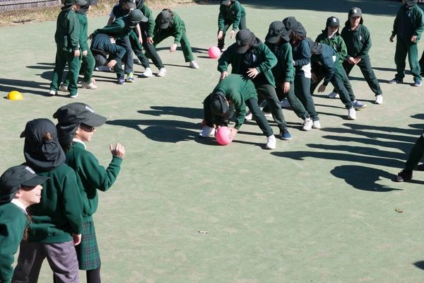 St Francis Xavier Catholic Primary School Ashbury - students in line passing the the ball at school
