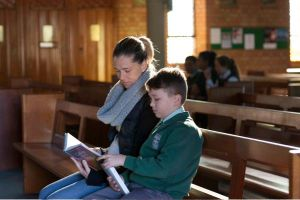 St Francis Xavier Catholic Primary School Ashbury- parent and student reading bible in a church
